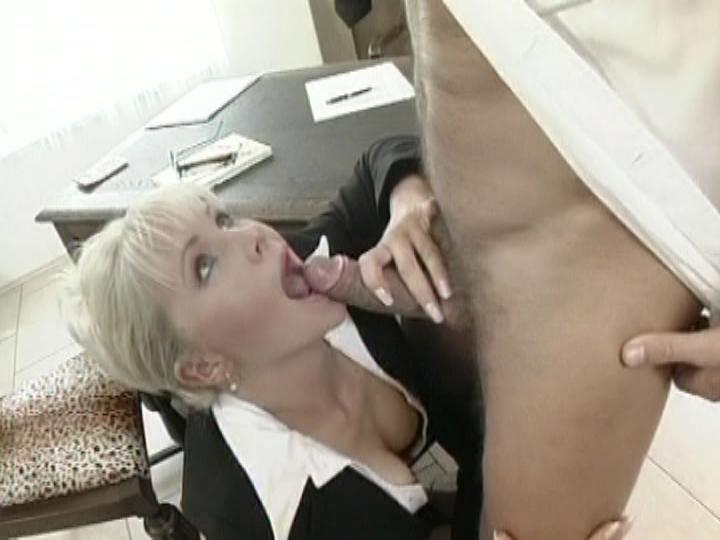 Secretaries / This clip from Secretaries by Combat Zone features Kathy Anderson in her office suit on her knees with a big hard cock in her mouth, licking and sucking on it like a starving woman, getting all she can.