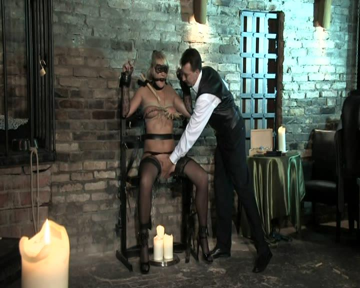"""Schmerzgeil / Master Costello makes his blonde submissive writhe and moan in pleasure and pain with tit punishment, forced orgasms, and more in """"Schmerzgeil."""""""