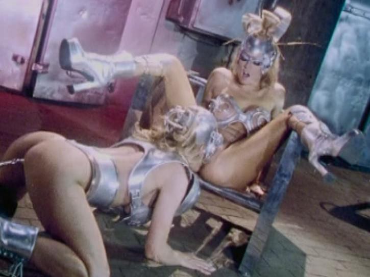 Hell on Heels / This clip from Hell on Heels by Wicked Pictures features Jenna Jameson in a futuristic fembot sex scene, a wired up silver gynoid, fucking the other cyber-slut with anal beads and her fingers.